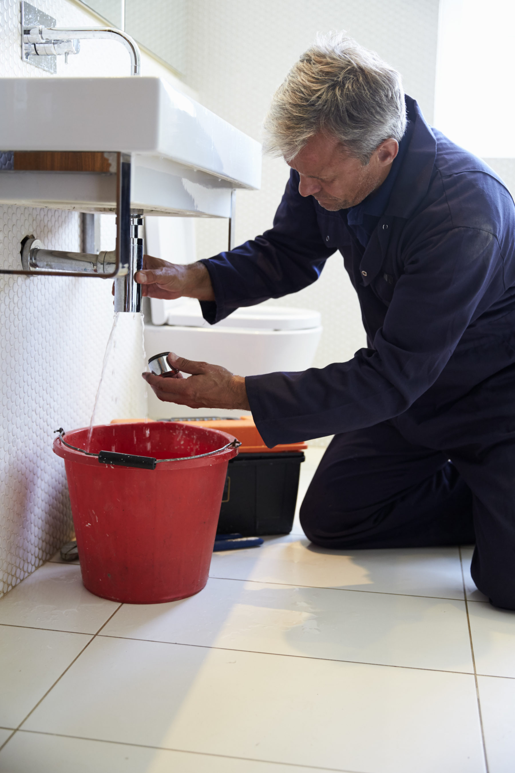 Plumber Working On Sink In Bathroom
